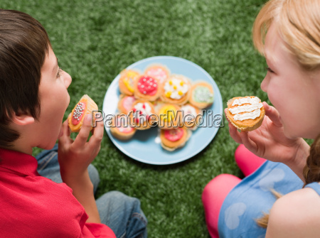 a boy and girl having cakes