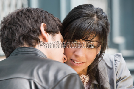 a young man whispering to a