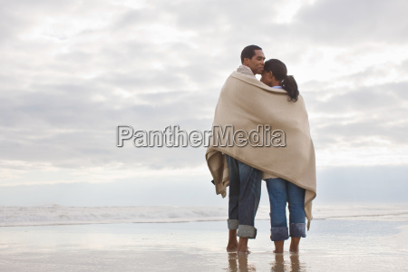 couple in blanket by the sea