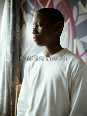 teenage boy standing in bedroom