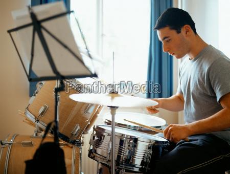 teenager spielt die trommeln