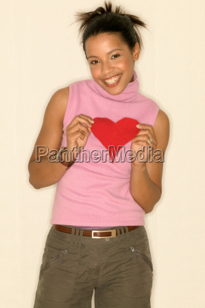 young woman holding a heart shape