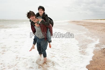 man giving girlfriend piggyback in the