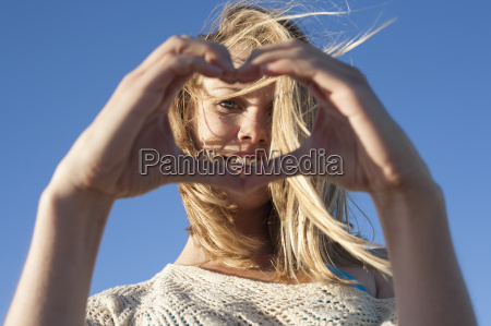 portrait of young woman making heart