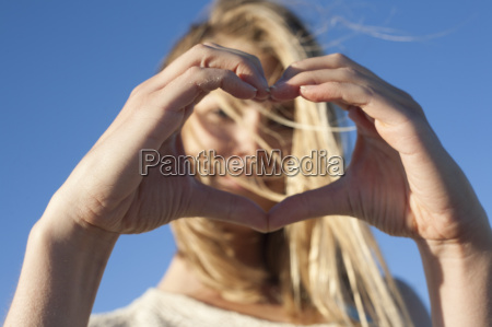 young woman making heart sign with