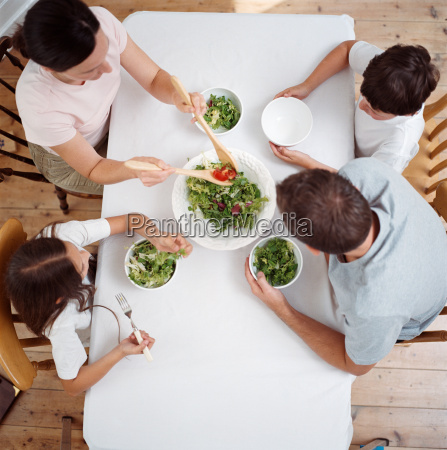 family eating salad at table