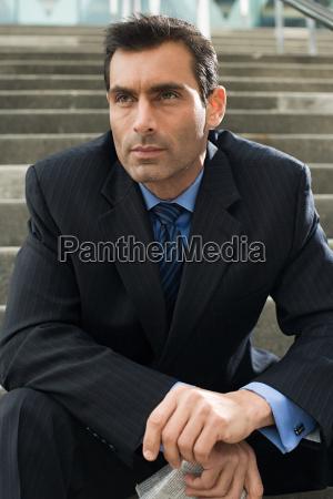 a businessman sitting on steps holding