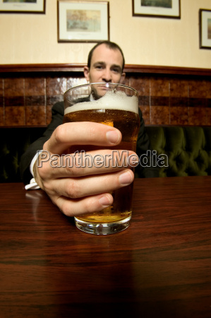 businessman holding a pint of lager
