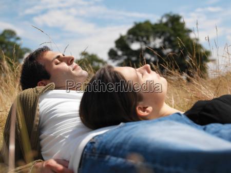 couple sunbathing in field