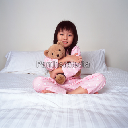 young girl cuddling bear on bed
