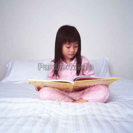 young girl reading on bed