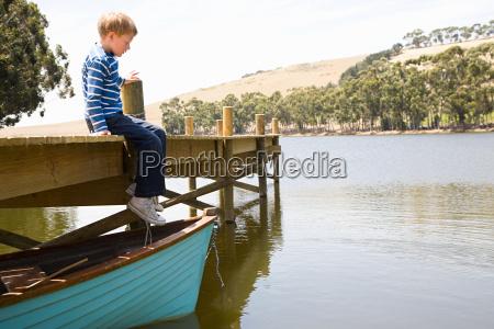 boy sitting alone on jetty