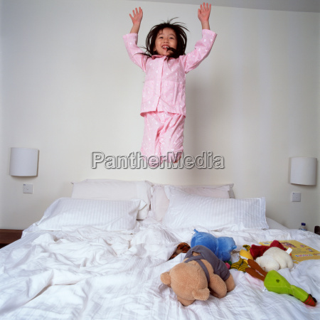 young girl jumping on bed