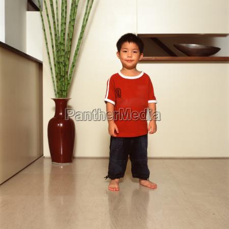 boy standing near houseplant