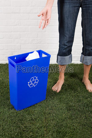 a woman throwing paper into a