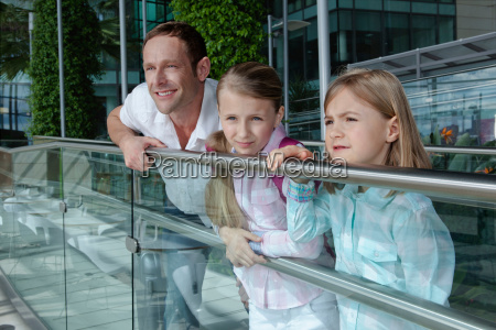 father with two daughters leaning on