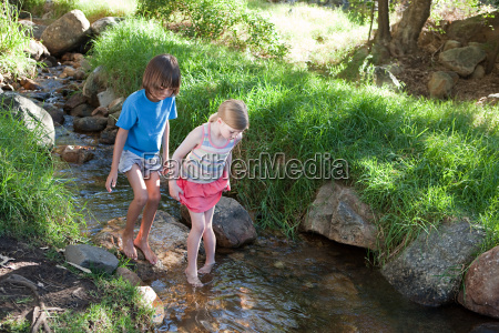 boy and girl walking in river