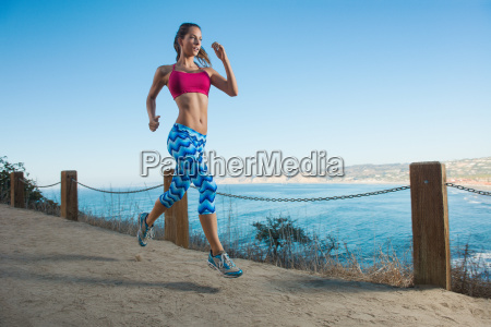 young woman running on path by