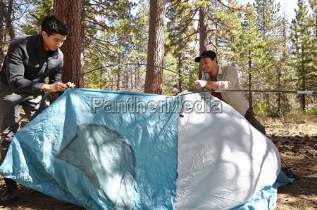 two young men putting up tent