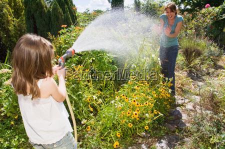 girl spraying water at mother