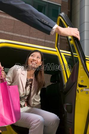 female shopper leaving taxicab