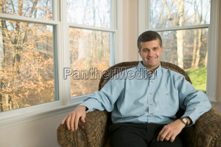 mid adult man relaxing in chair