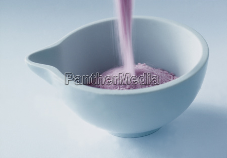 pink bath salts being poured into