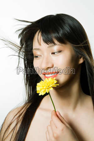 young woman holding yellow flower