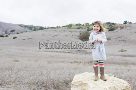 portrait of girl standing on rock