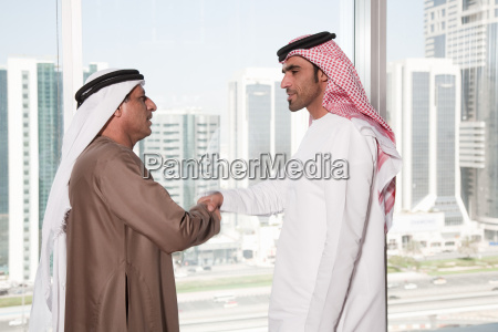 dubai businessmen shaking hands by window