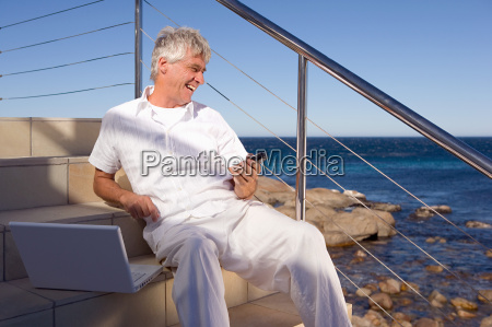 man by the sea with laptop