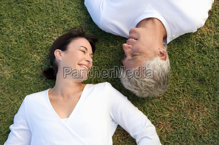 mature couple lying on the grass