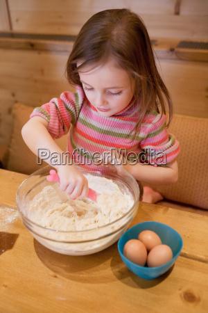 young girl making cake