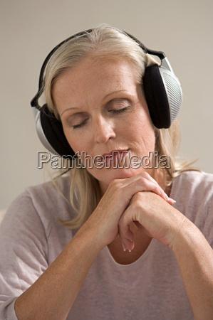 mature woman wearing headphones