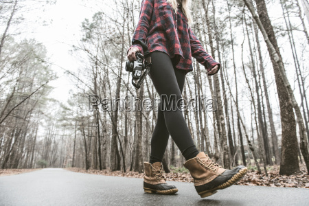 young female photographer strolling on rural