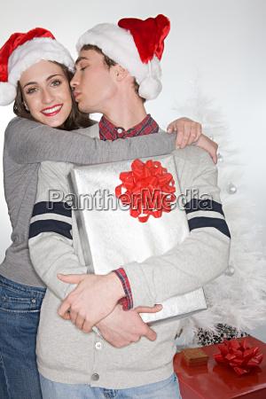 couple in santa hats kissing