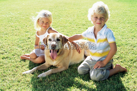 brother and sister with labrador