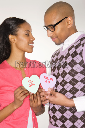 young couple holding heart shapes