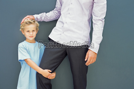 boy holding his fathers leg
