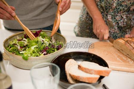 close up of couple preparing food