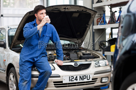 young mechanic drinking coffee on car