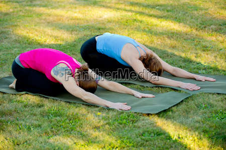 two women stretching on yoga mats