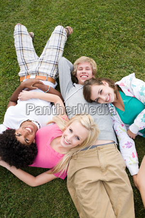 teenage friends lying on grass