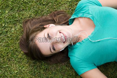 girl on grass wearing earphones