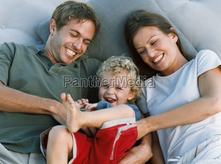 mother and father tickling son