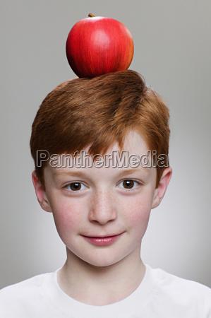 boy balancing an apple on his