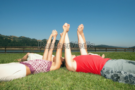 friends lying down and holding hands