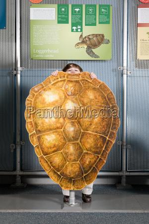 boy standing behind loggerhead sea turtle