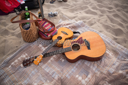 guitars and bags on picnic blanket