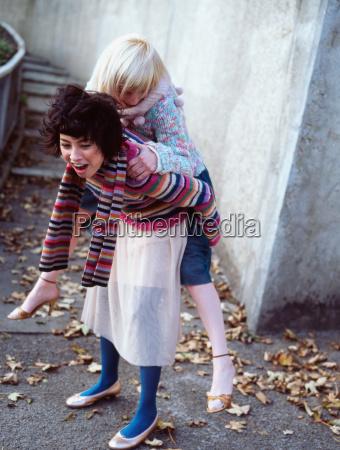 woman giving her friend a piggyback
